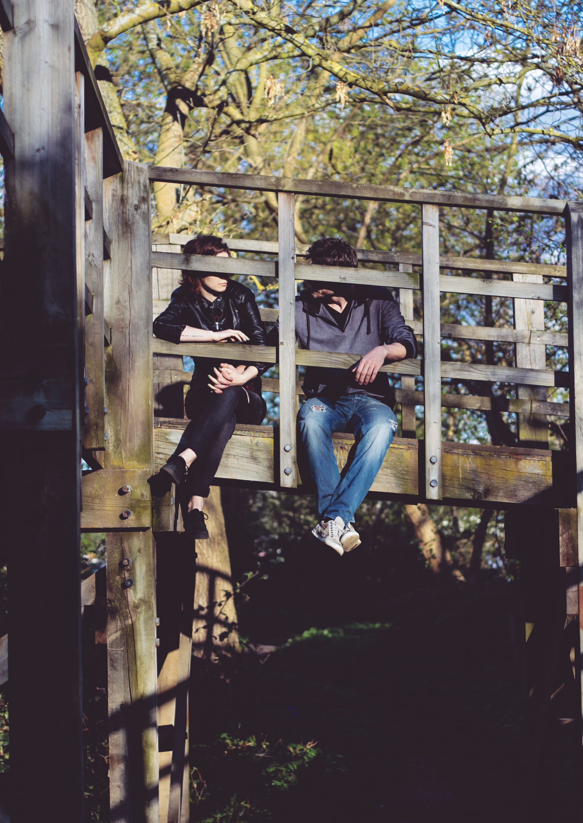 couple sitting on bridge